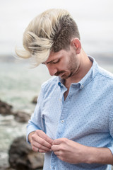 Young boy, with blond hair, fastening the buttons of his light blue shirt, outdoors, near the sea.