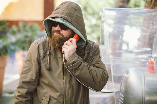 Portrait of young bearded man using public phone wearing hoodie (jacket) and black sunglasses - informant, spy, secret agent and fake news concept