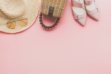 Summer fashion background on pink, trendy straw bag, fedora hat, heeled shoes and yellow sunglasses, flat lay, top view, selective focus Wall mural