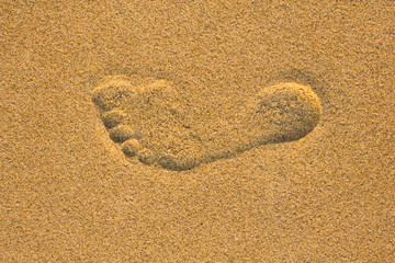 left foot print in yellow sand close up