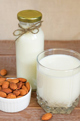 Homemade Almond milk in a bottle and nuts in white porcelain bowl on wooden background
