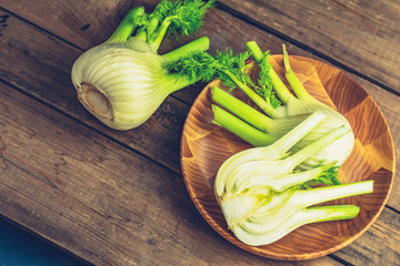 Fresh fennel bulbs in plate on wooden background.
