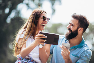 Cheerful young couple sitting on a park bench and uses a digital tablet for online shopping