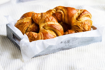 Croissant for breakfast on white woolen surface