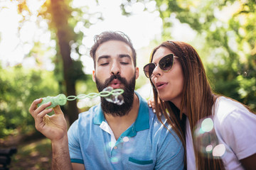 Couple sitting on the park bench and blowing soup bubbles on beautiful sunny day
