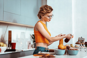 Positive nice woman cooking a healthy breakfast