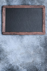 Blackboard with frame on concrete background top view with copy space