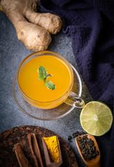 Turmeric tea and ingredients on dark, top vew