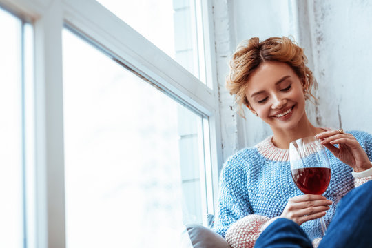 Cheerful positive woman looking at the wine