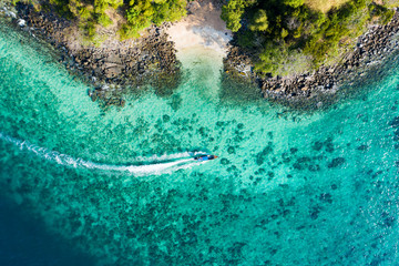 Wall Mural - View from above, aerial view of a traditional long-tail boat sailing near a stunning barrier reef with a beautiful small beach bathed by a transparent and turquoise sea. Phi Phi Island, Thailand.