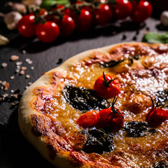 Traditional Italian pizza, vegetables, ingredients on a dark background. Pizza is cooking in the oven. Pizza menu.