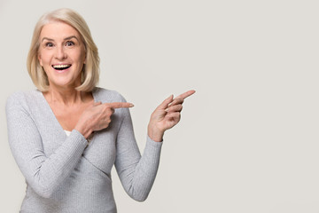 Amazed excited mature woman pointing at copyspace isolated on background