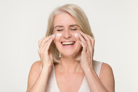 Happy old woman apply anti aging cream isolated on background