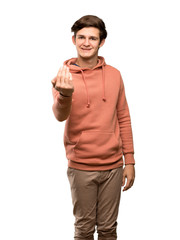 Teenager man with sweatshirt inviting to come with hand. Happy that you came over isolated white background