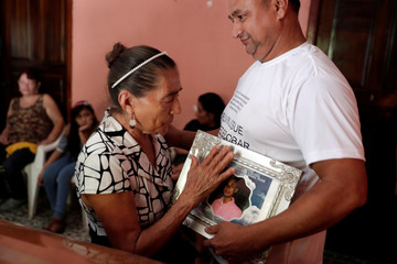 Relatives of Melvin Josue Gomez, a Honduran migrant who died after falling off a moving vehicle while traveling with other migrants on the caravan of Central Americans en route to the U.S., hold a picture during his wake at his home in Chamelecon