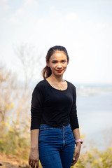 Women white skin lovely brown hair a small woman red lips wearing a black shirt wearing a blue gene woman stand  poses photography portrait which has both trees and water in the back in the park.