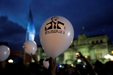 A demonstrator holds a balloon with an image depicting Guatemala's President Jimmy Morales as a clown during a protest against Guatemala's his decision to not renew the International Commission Against Impunity, in Guatemala City