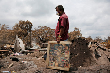 A resident holds framed pictures of his family, recovered from his house in an area affected by the eruption of the Fuego volcano, in San Miguel Los Lotes