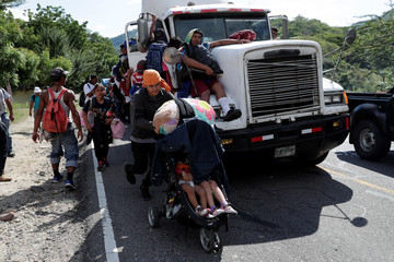 Central American migrants, part of a second wave of migrants heading to the U.S., are seen hitchhiking on a truck and on foot as they continue their journey to the Mexican border, in Chiquimula