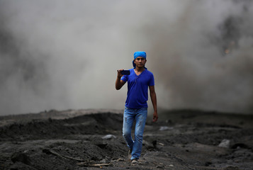 A resident takes pictures with his cellphone in an area affected by the eruption of the Fuego volcano at San Miguel Los Lotes in Escuintla