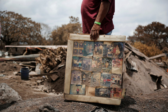 A resident holds framed pictures of his family, recovered from his house in an area affected by the eruption of the Fuego volcano, in San Miguel Los Lotes in Escuintla