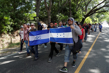 Honduran migrants, part of a second wave of migrants heading to the U.S., hold Honduran flags as they continue their journey to the Mexican border with other Central American migrants, in Chiquimula