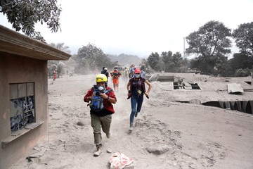 Media members reacts at an area affected by the eruption of the Fuego volcano in the community of San Miguel Los Lotes in Escuintla