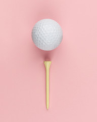Golf ball and wooden tee on pink background closeup