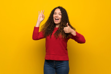 Teenager girl with red sweater over yellow wall showing ok sign with and giving a thumb up gesture