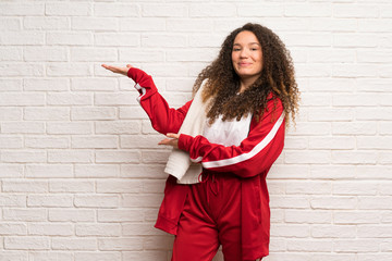 Teenager sport girl with curly hair extending hands to the side for inviting to come