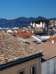 Mediterranean style shingle tiles are seen on rooftops  Cannes, France, Europe  Old Cannes in distance of harbor