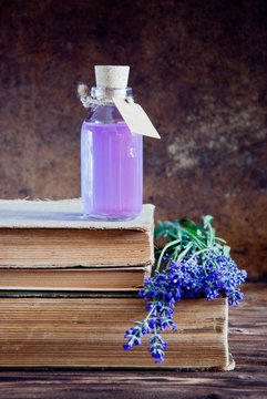 Lavender flowers, lavender essential and old books on a wooden background