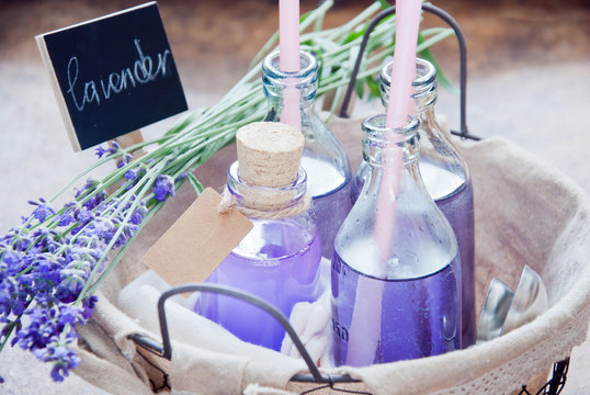 Lavender Lemonade and syrup in the basket at Farmers Market on a wooden background