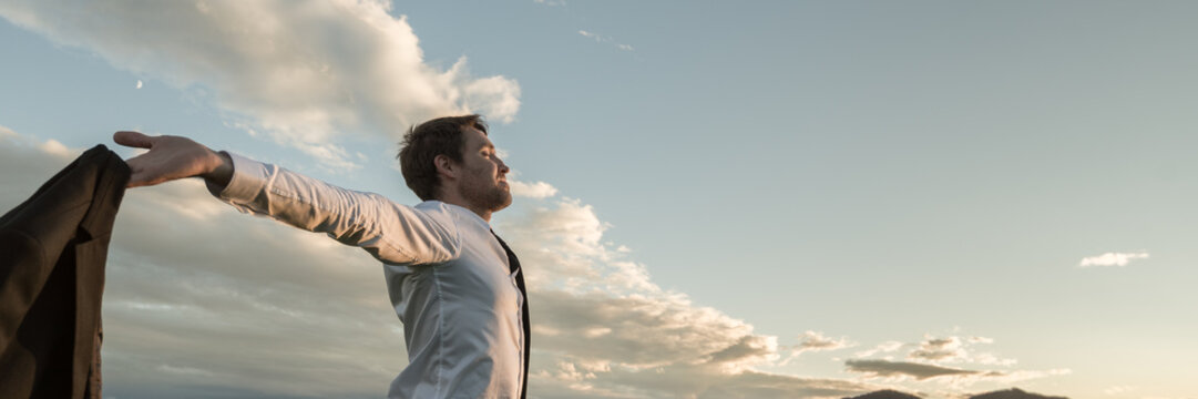 Businessman embracing life standing under cloudy sky