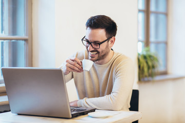 Happy young man, wearing glasses and smiling, as he works on his laptop to get all his business done
