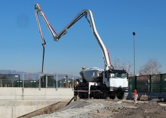 Cement mixer truck with its pump is preparing to put concrete on a foundation of the new building under construction