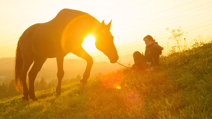 SILHOUETTE: Big stallion grazing at sunset while girl sits nearby in the grass.