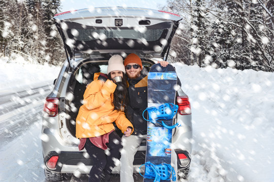 Young couple is sitting in the back trunk of suv car on roadside of winter road and drinking hot tea from thermos. Family trip to ski resort. Winter holidays adventure. travelling lifestyle concept.