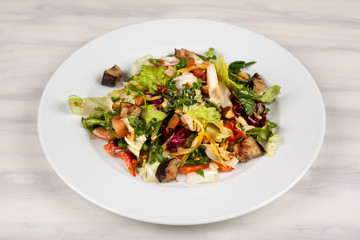 Eggplant salad with vegetables and walnuts on a white plate.