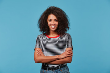 Self-confident happy young African American woman with long curly dark hair laughing smiling against blue background standing with arms crossed Fototapete