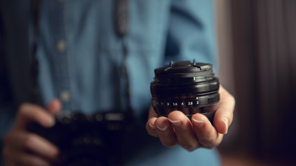Photographer showing lens camera while hand using camera.