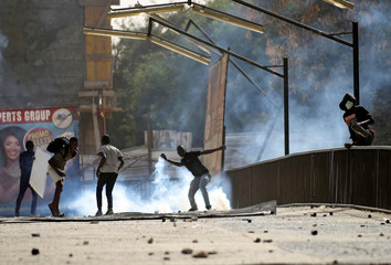 Student protestors throw rocks towards riot police at a university campus following provisional results showing President Macky Sall winning another term in office in Dakar