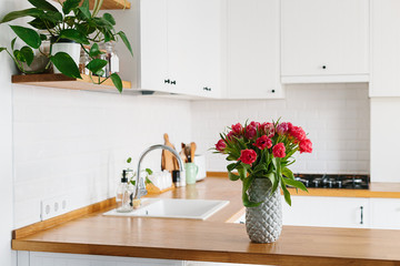 Tulips bouquet in vase standing on wooden countertop in the kitchen. Modern white u-shaped kitchen in scandinavian style.