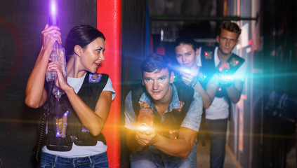 Portrait of happy young friends playing laser tag  game  with la