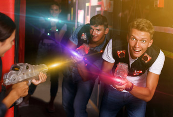 friends standing with laser guns during laser tag game