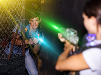 couple holding colored laser guns during laser tag game