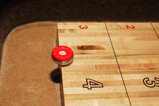 red shuffleboard disc on the table at five point mark. Shuffleboard game in progress, night, interior.