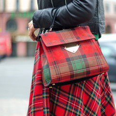 Bag closeup in female hands. Bright image, style. Girl in a red plaid skirt.