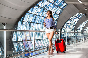 The airport terminal for departure, a beautiful lady in blue shorts and a blouse with a red travel suitcase awaits boarding. Travel, flight around the world.