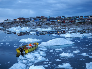 Small motorboat anchored by arctic town